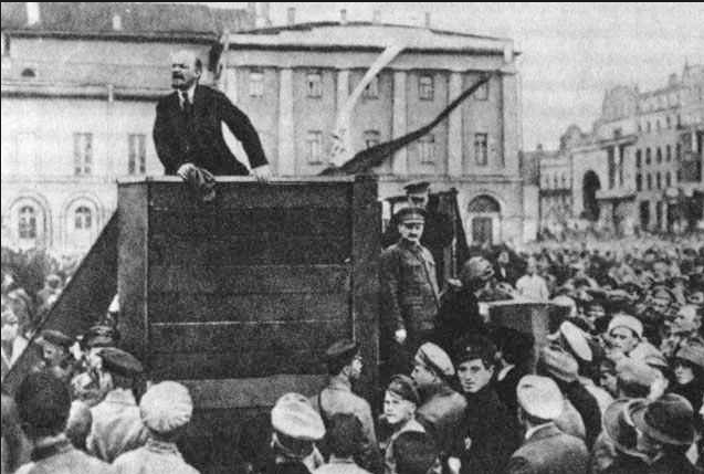 Vladimir Lenin, leader of the Bolsheviks, speaking at a meeting in Sverdlov Square in Moscow, with Leon Trotsky and Lev Kamenev adjacent to the right of the podium.