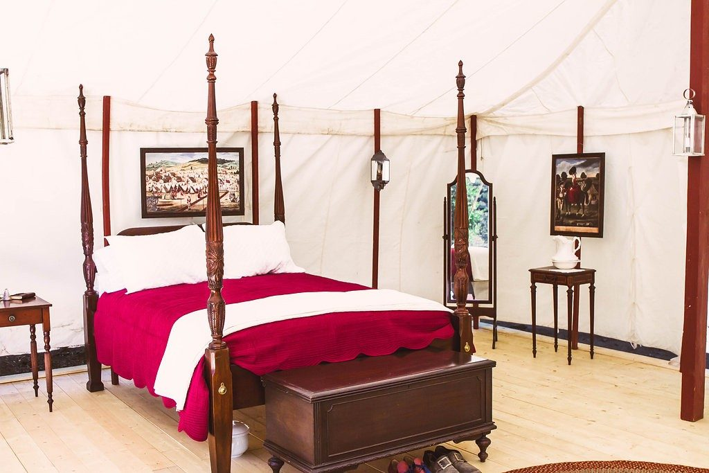 "Book your overnight ""glamping"" experience in a charming 20×20 colonial marquee tent fully furnished with a comfy four poster queen bed, luxurious linens, private en suite dining area, and romantic candlelight."