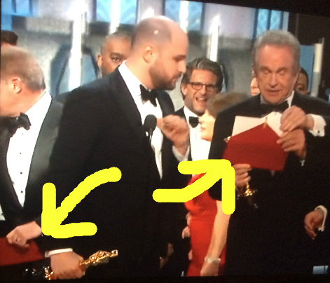 Left arrow shows the INCORRECT envelope being taken far away as Beatty holds the now-correct envelope.